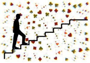 Homme montant des escaliers fictifs, entouré 'un nuage des figures de jeu de carte (trèfle, coeur, pique, carreau)