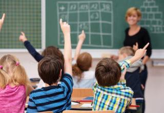 les élèves d'une classe lèvent tous la main pour participer
