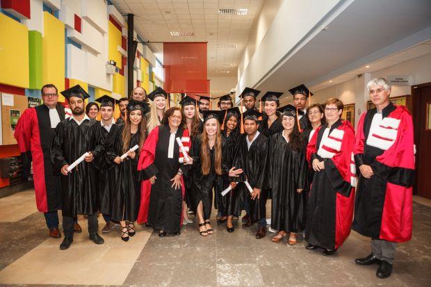 les étudiants posent avec leurs diplômes et leurs professeurs