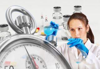 une laborantine effectue un mélange derrière un chronomètre en premier plan