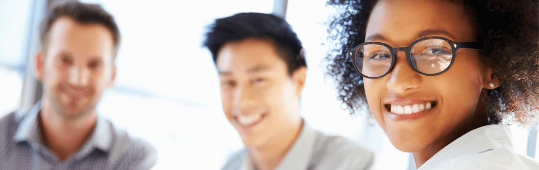 Une femme et ses collaborateurs sourient à la caméra