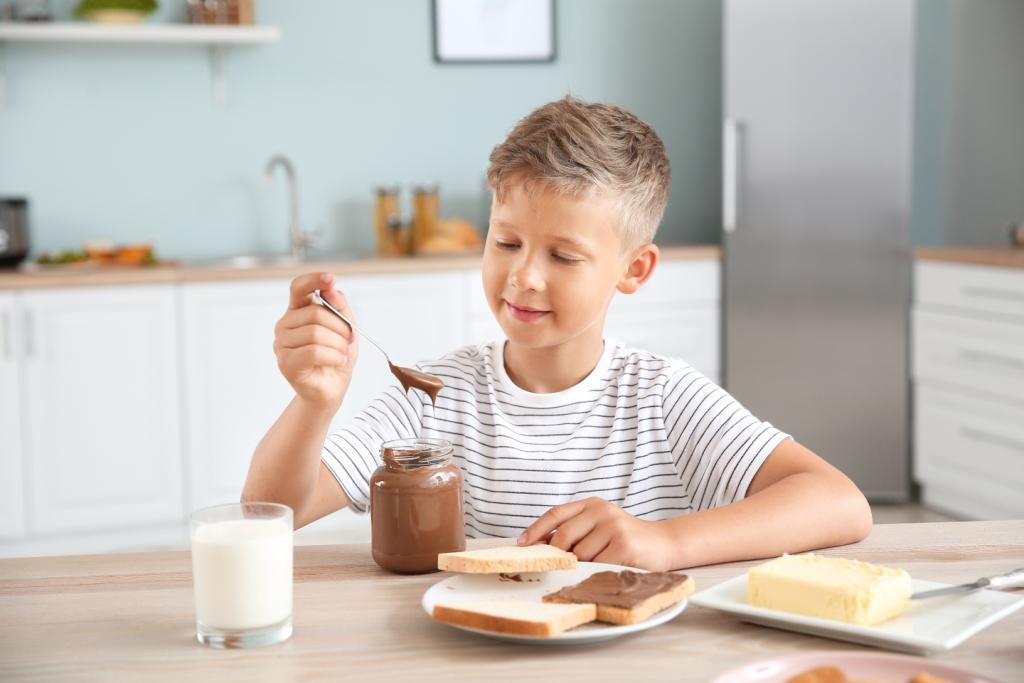Un garçon en train de prendre le petit déjeuner avec des tartines